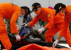 Indonesia names first plane crash victim, steps up 'black box' hunt