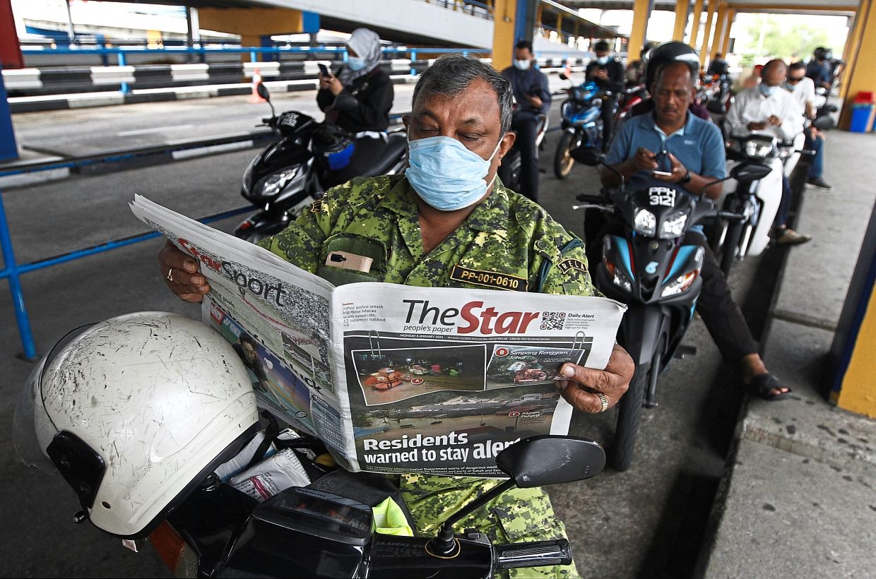 Selvarajah reading The Star while waiting for the ferry to arrive at the Raja Tun Uda ferry terminal in George Town.