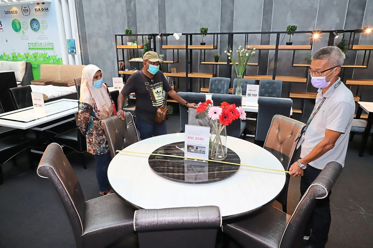 An exhibitor providing the measurement of a dining table to customers at the Perfect Livin expo at Setia SPICE Convention Centre in Relau, Penang.