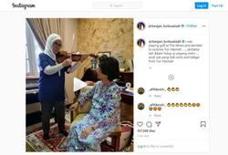 Queen plays the violin in front of Dr Siti Hasmah