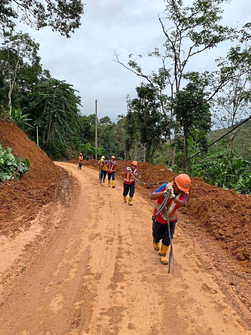 Mohd Lokman and his teammates lugging electricity cables across hilly and muddy areas in Raub, Pahang, for power supply.