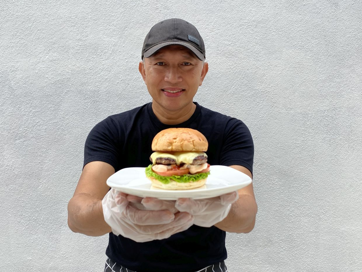 Zack with a homemade burger. When the time is right, he plans to expand the menu beyond burgers.