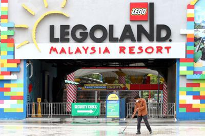 A worker mops the entrance of Legoland Malaysia Resort in Johor. Theme parks are closed during the MCO 2.0 period, which would last until Jan 26, 2021. THOMAS YONG/The Star