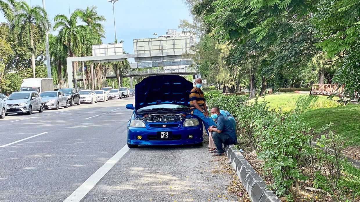 A family waiting by the roadside along Tun Dr Lim Chong Eu Expressway as their car engine overheated while caught in heavy traffic.