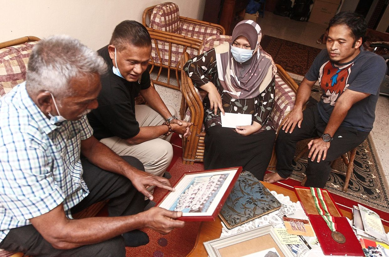 (From left) Nadarajan and Scully viewing some old photos of Mohamad before presenting a donation to Dr Mardhiana and her husband Mohd Khairi Bhalia in Teluk Ayer Tawar, Penang.