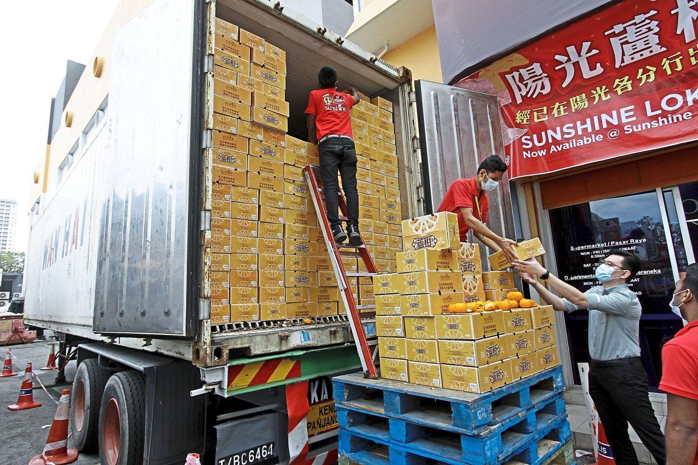 Festive fruits: Wong (in blue shirt) receiving his first shipment of mandarin oranges at Bayan Baru. — CHAN BOON KAI/The Star