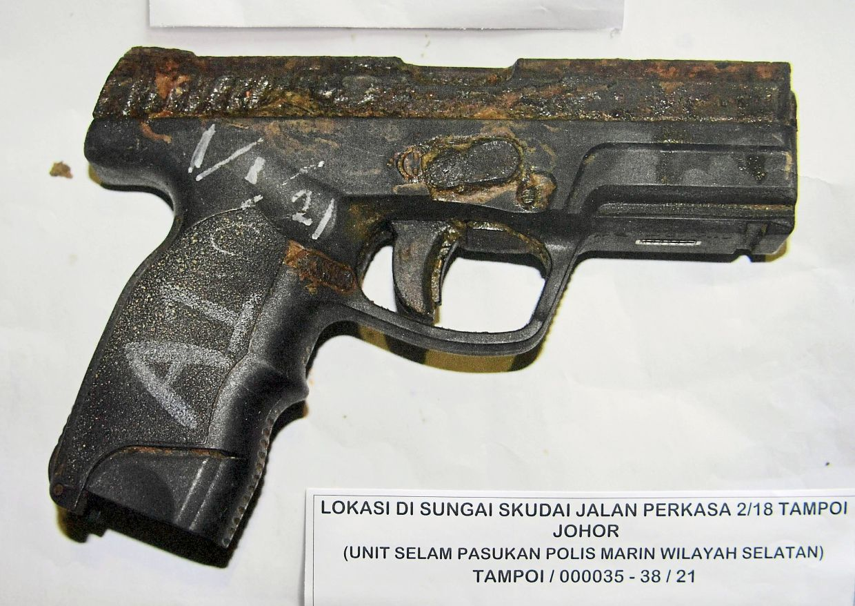 Smoking gun: The real semi-automatic pistol that was found among airsoft rifles in the river. — Bernama