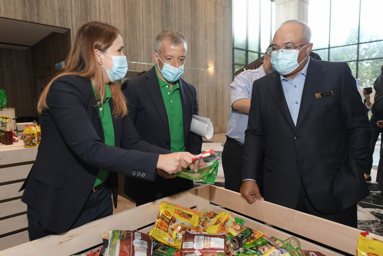Raja Nurmaria Murni, Consumer Marketing Manager for MILO with Juan Aranols, Nestlé Malaysia CEO (left) explaining to the Mayor of Petaling Jaya about Nestlé's recyclable packaging at the launch of the kerbside collection programme in collaboration with the Petaling Jaya City Council.