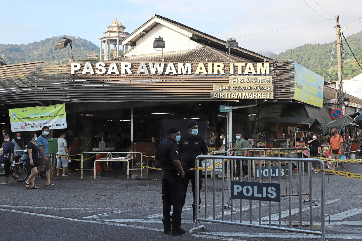 Police manning a barricade put up in front of the Ayer Itam market in Penang. — Photos: LIM BENG TATT/The Star