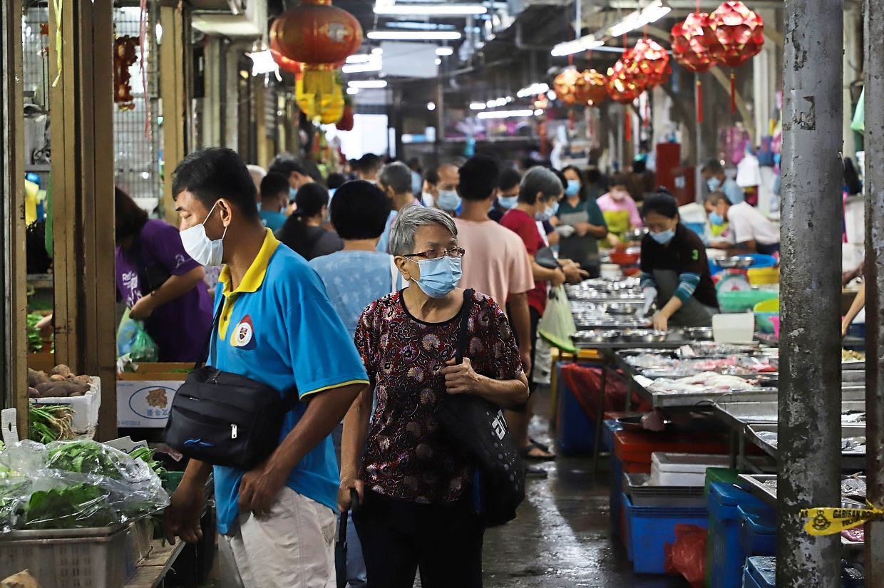 Market-goers buying daily essential items inside the Ayer Itam market.