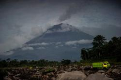 Indonesian volcano spews ash as officials grapple with disasters