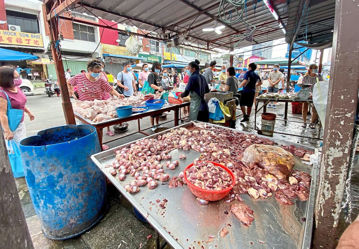 Market-goers keeping some distance from each other at a stall selling chicken along Jalan Penaga near the Jelutong wet market.