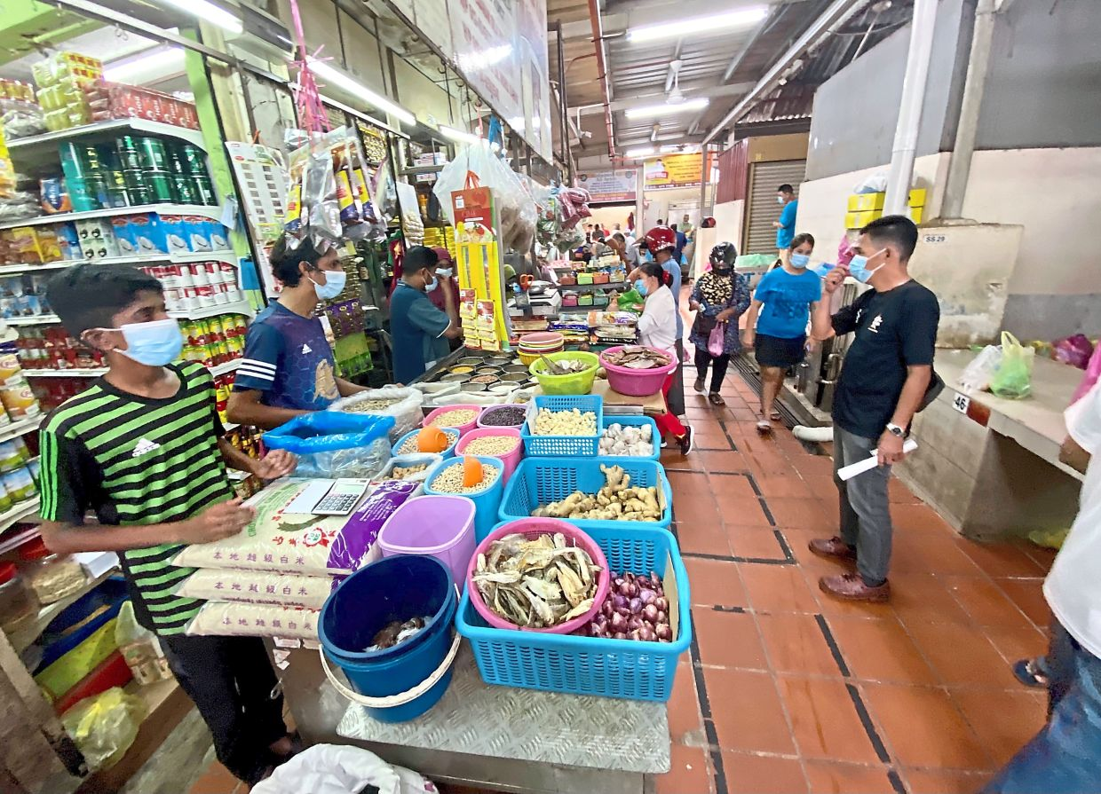 Visitors shopping for essentials inside the market building. Only 35 people are allowed inside at any one time.