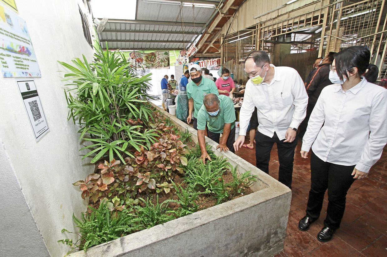 Lee (with yellow mask) and Tan (right) being briefed by an MBPP worker on the landscaped area near the public toilet at Pulau Tikus market in George Town. — Photos: CHAN BOON KAI/The Star