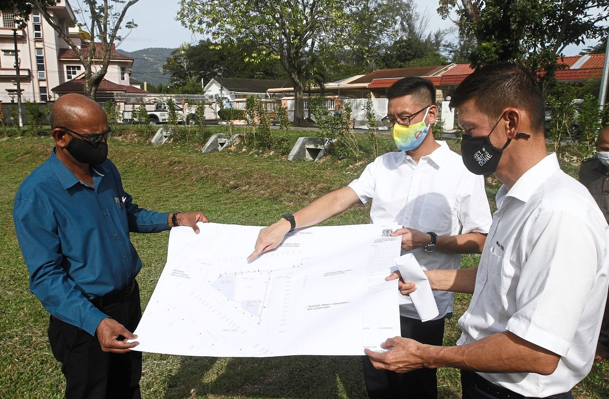 (From right)  Ong and Zairil discussing the flood mitigation project during  a visit to the  project site in Solok Van Praagh in Jelutong, Penang.  – Photos:  ZHAFARAN NASIB/The Star