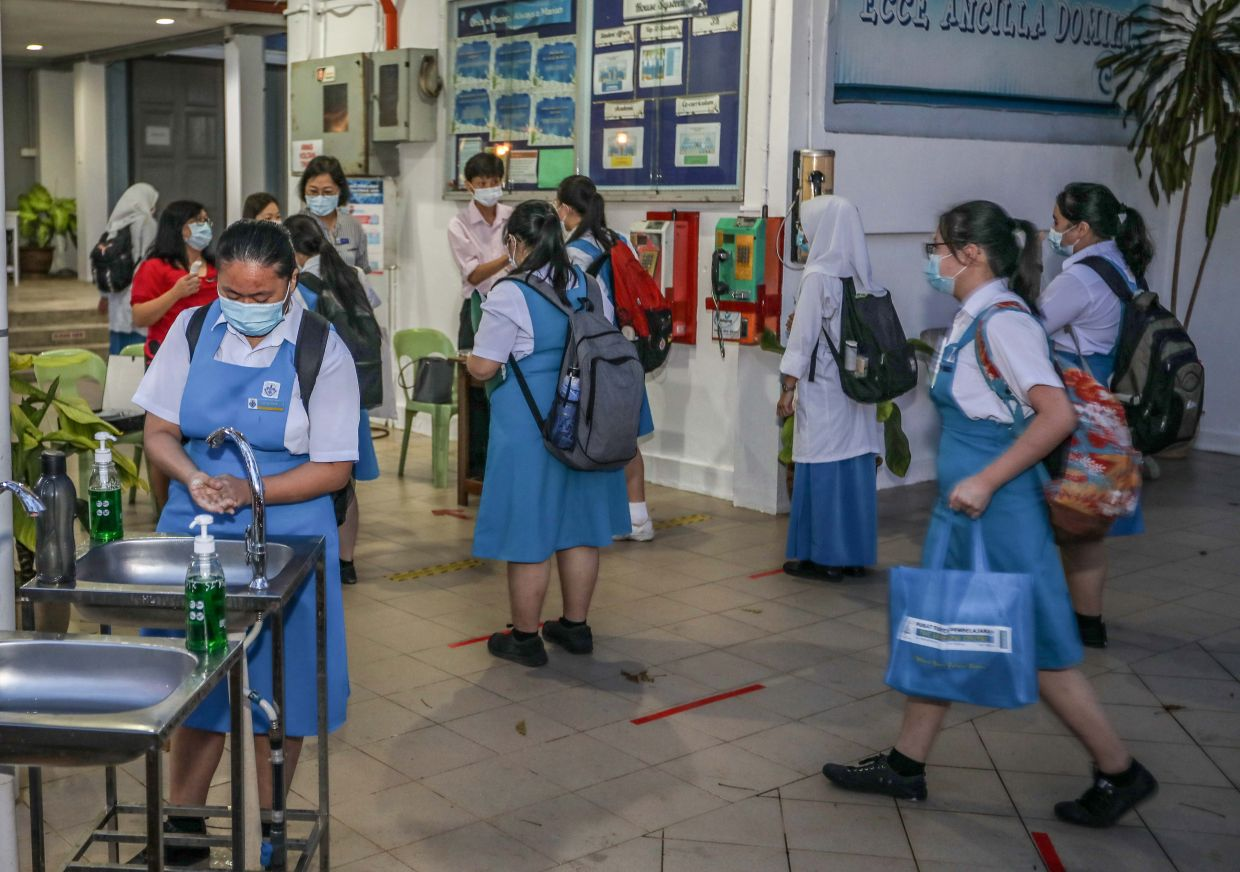SMK St Mary students sanitising their hands before entering the classroom. Some 104 Form Five students are attending the school in four classes.