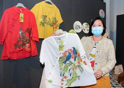 Chinese brush painter and students feature their handiwork on clothing, bags and fans