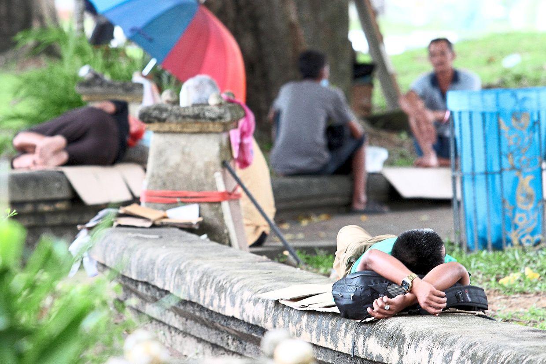 Homeless individuals sleeping on flattened cardboard boxes or chatting among themselves at Laman Tun Sri Lanang outdoor carpark, Johor Baru.