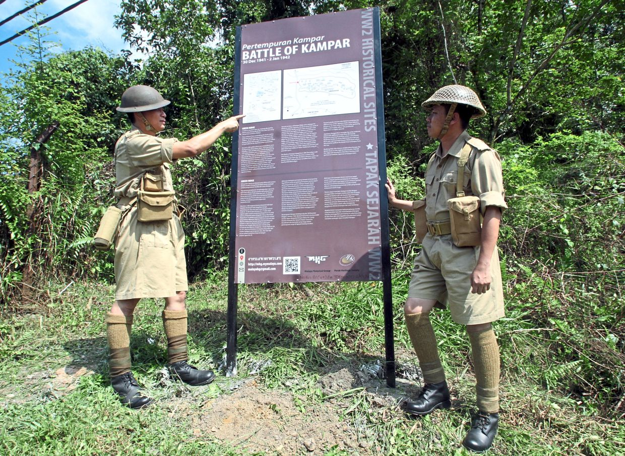 Shaharom (left) and fellow researcher Norhisham Zulkiflee putting up the information board at Green Ridge Kampar last year. — Filepic