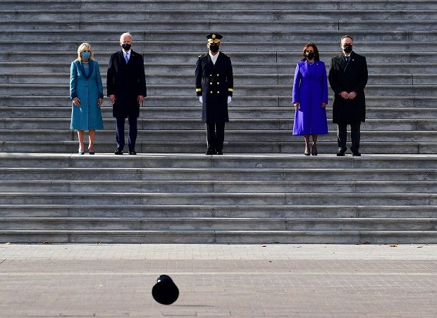 High winds forces a hat to blow by US President Joe Biden, First Lady Jill Biden, US. Vice President Kamala Harris and First Gentleman Douglas Emhoff as they stand on the east steps of the US Capitol watching the troops march in Washington, DC on January 20, 2021. -AFP