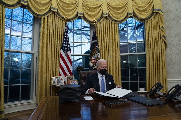 President Joe Biden signs a series of executive orders in the Oval Office of the White House, Wednesday, Jan. 20, 2021, in Washington. -AP