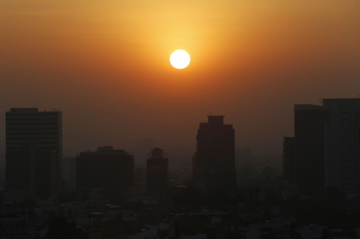 In file photo, the sun rises amid smog during the dry season in Mexico City.