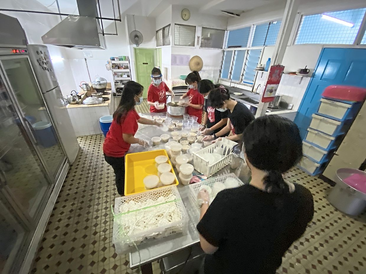 The kitchen crew cooking and packing chicken porridge for distribution.