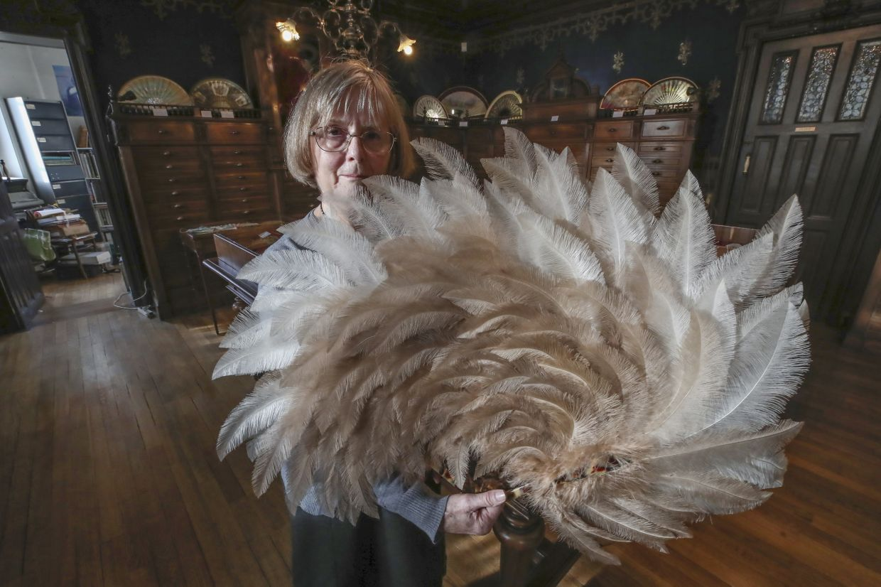 Hoguet takes out a feather fan from the museum's collection in Paris. Photo: AP
