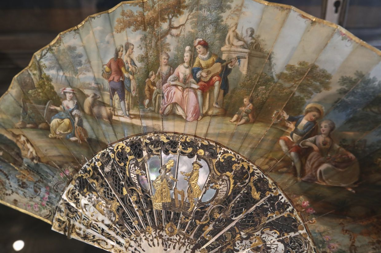 A hand fan representing a musical relaxing moment (detente musicale) is pictured at the hand fan-making museum in Paris. Photo: AP