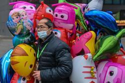 Wuhan marks a year since lockdown as Biden warns of 600,000 dead in US