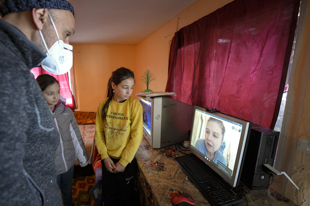 Children join Valeriu Nicolae on a video call with a voluteer that assists with homeschooling,  on a computer provided by the Good House, or Casa Buna in Romanian.