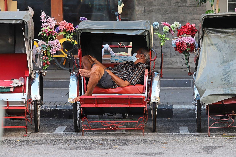 A trishaw rider having a snooze as there are no customers along Penang Road.