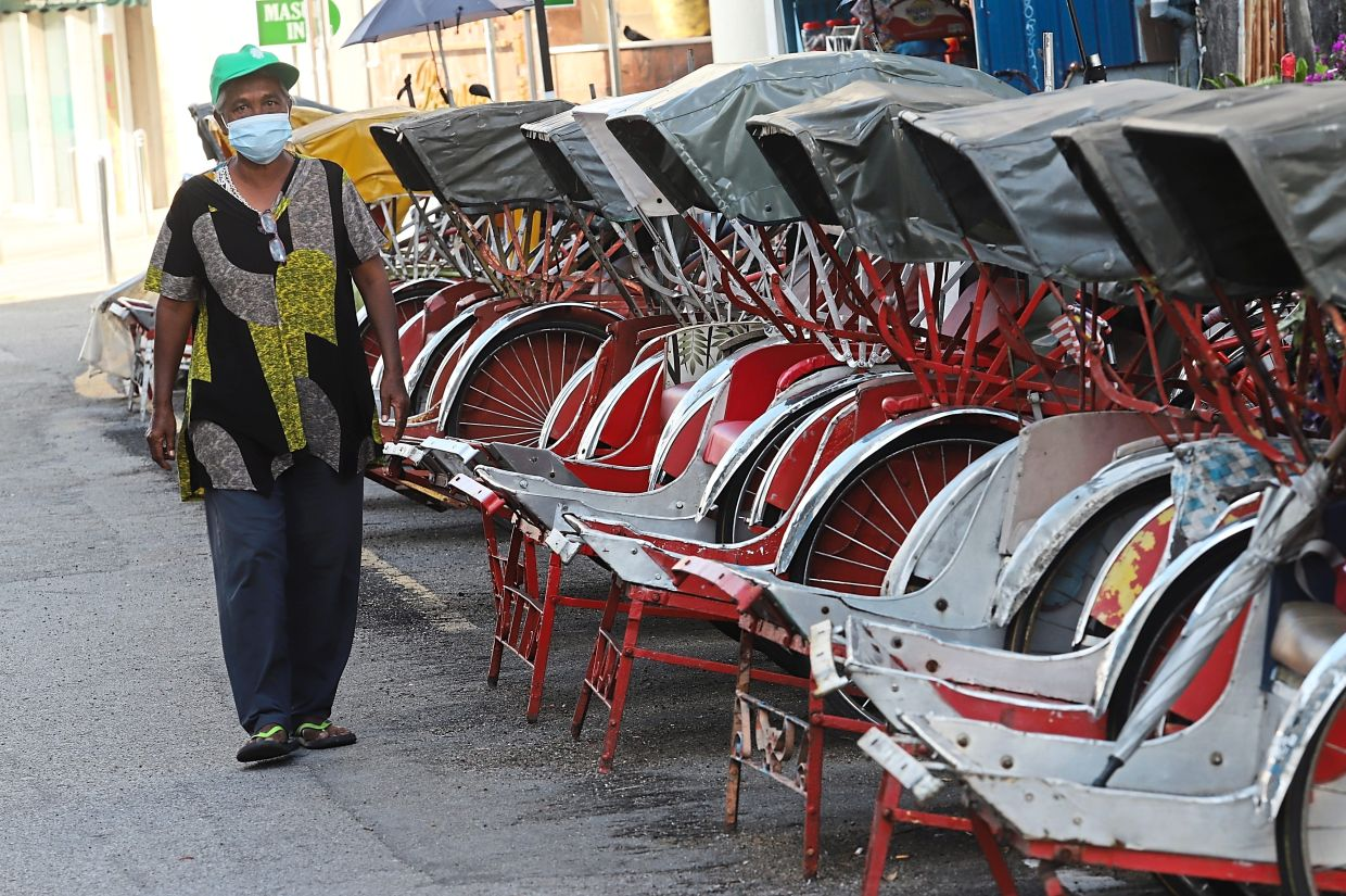 A row of empty trishaws parked along a once busy section of George Town.