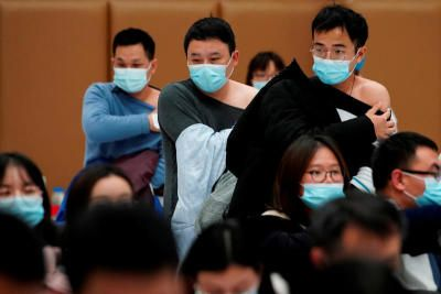 People stand at a vaccination site after receiving a dose of Covid-19 vaccine, during a government-organised visit in Shanghai, China on Jan 19, 2021. - Reuters