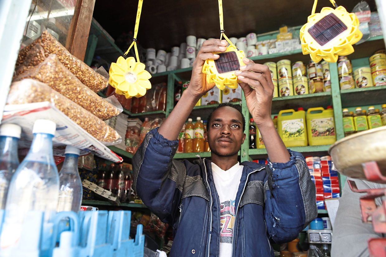 Lamps made by Berlin-based solar energy firm Little Sun hang at a shop in Ethiopia. —  Michael Tsegaye/Little Sun/dpa