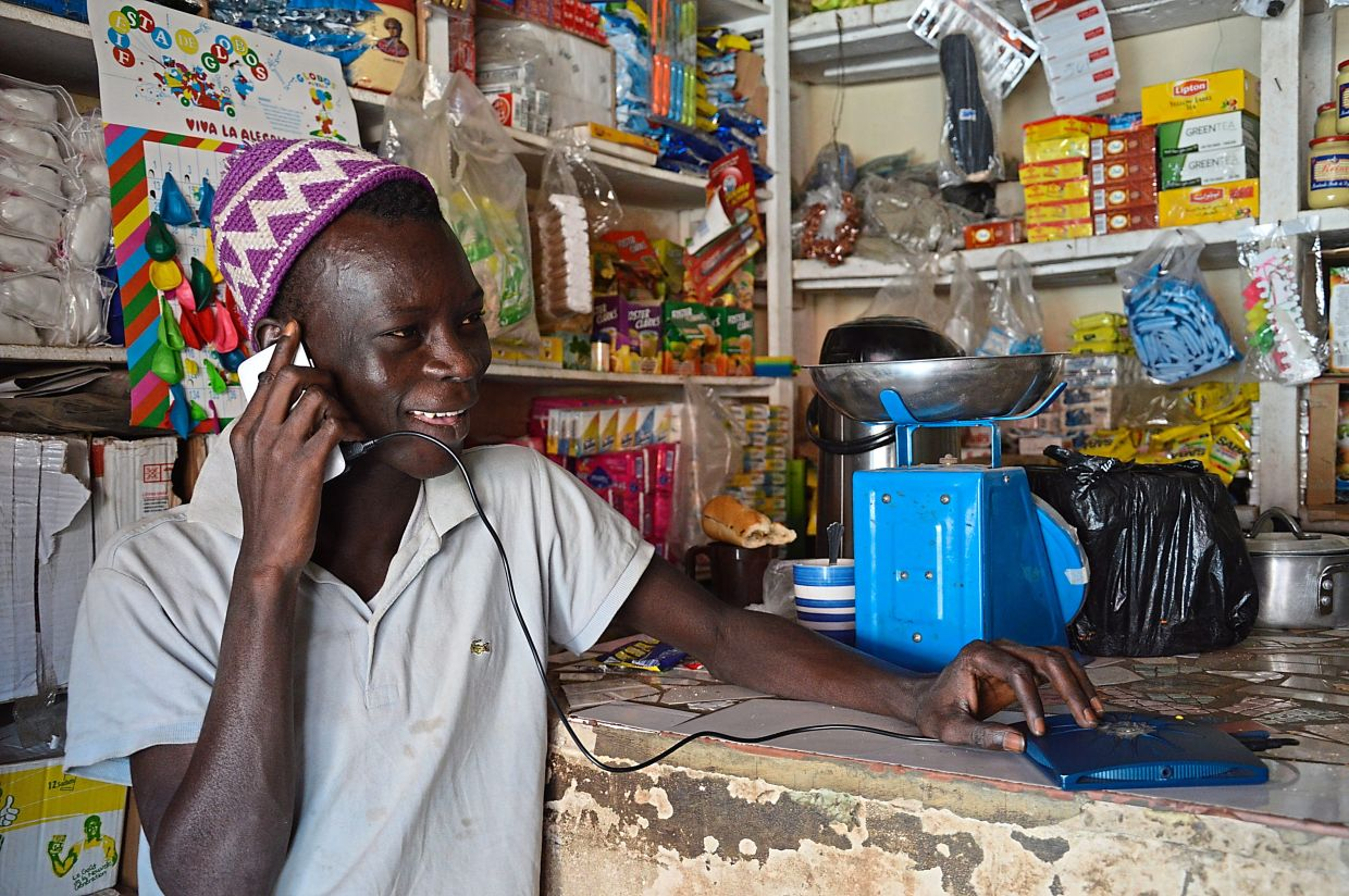 A man in Senegal charges his phone with a device made by the Berlin company Little Sun.