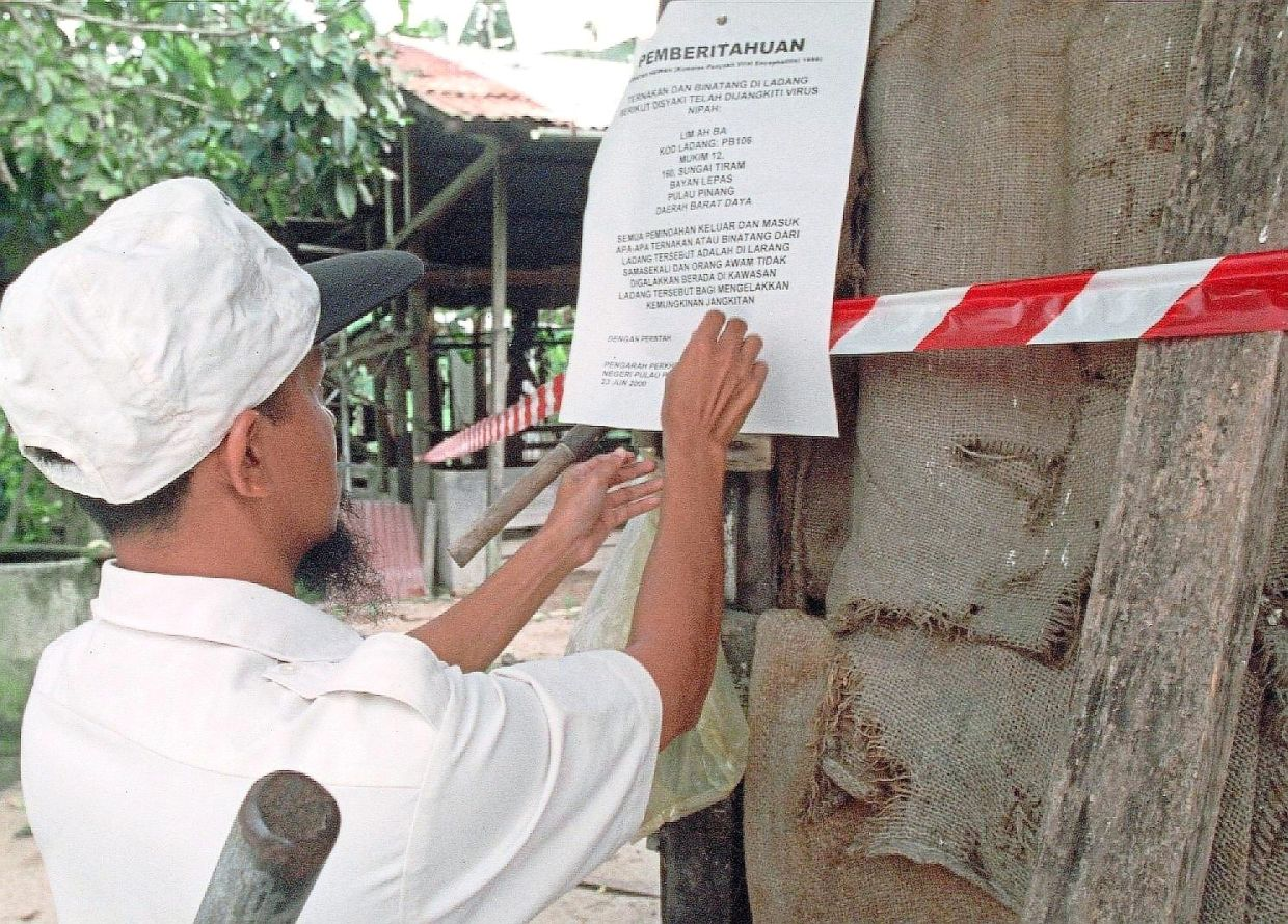 A government worker putting up a notice to seal off a pig farm where the animals are suspected to be carrying the Nipah virus in Sungai Tiram, Penang, in 2010. — Nanyang Siang Pau