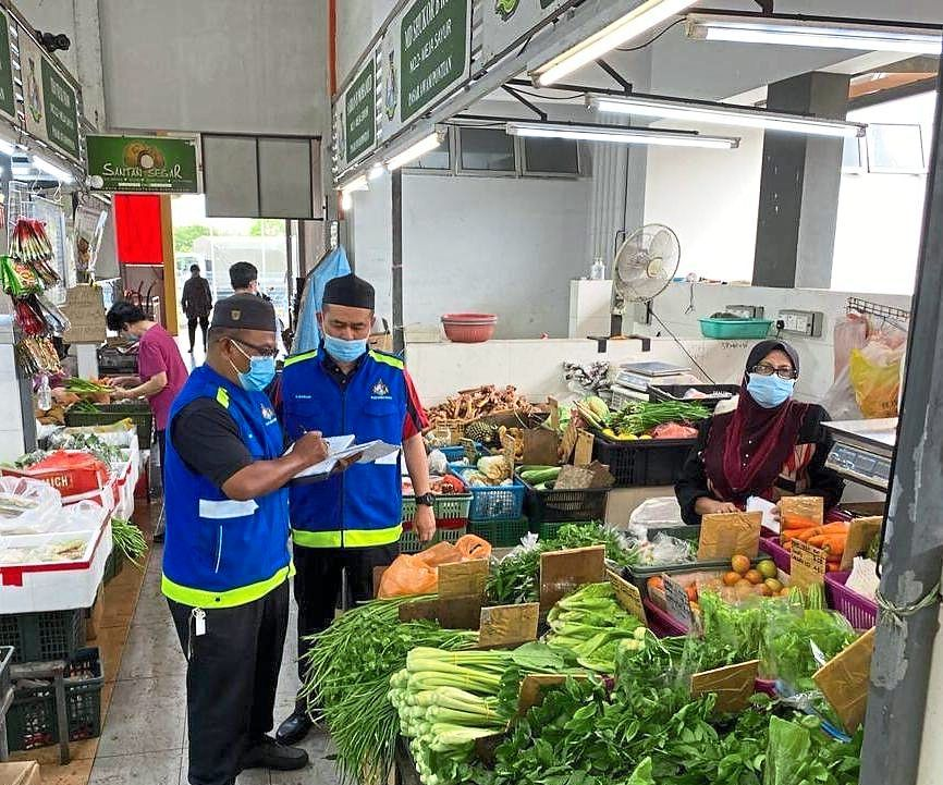 MDP enforcement officers conducting checks at a market to ensure the SOP is practised during the MCO.