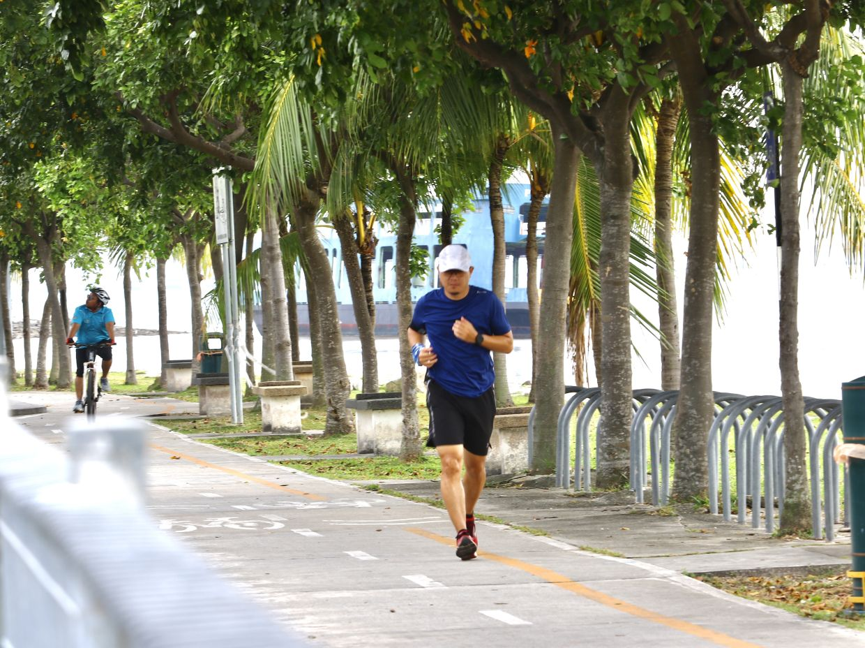 A jogger and a cyclist seen along the bicycle trail next to Queensbay Mall during MCO 2.0.
