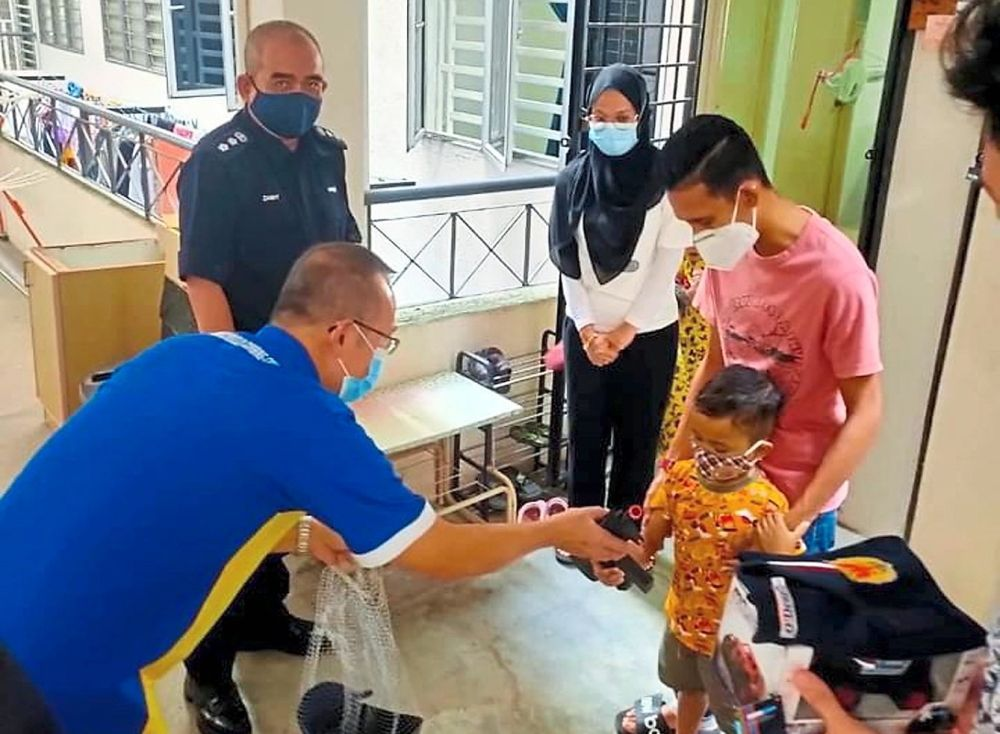 Goh handing over toys in the shape of police equipment to Mohammad Ammar. With them are (from right) father Mohamad Azuan Abdul Mutalib and mother Nur Syazwani as well as ACP Noorzainy.