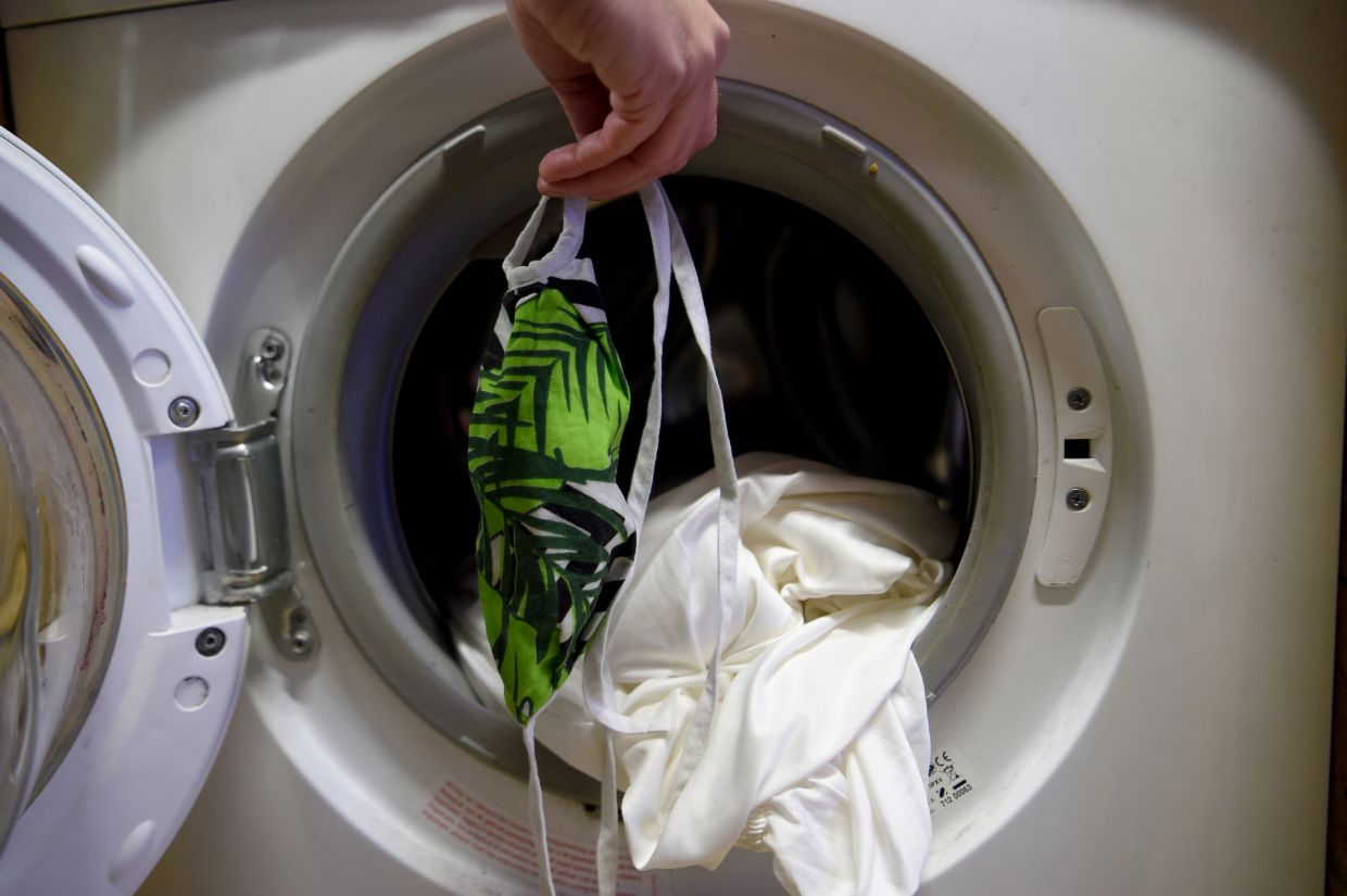 Laundry experts say cleaning a face mask in a washing machine is fine, so long as you pick the use a full or universal detergent in powder or granule form and set the machine to 60 degrees celcius. Photo: dpa