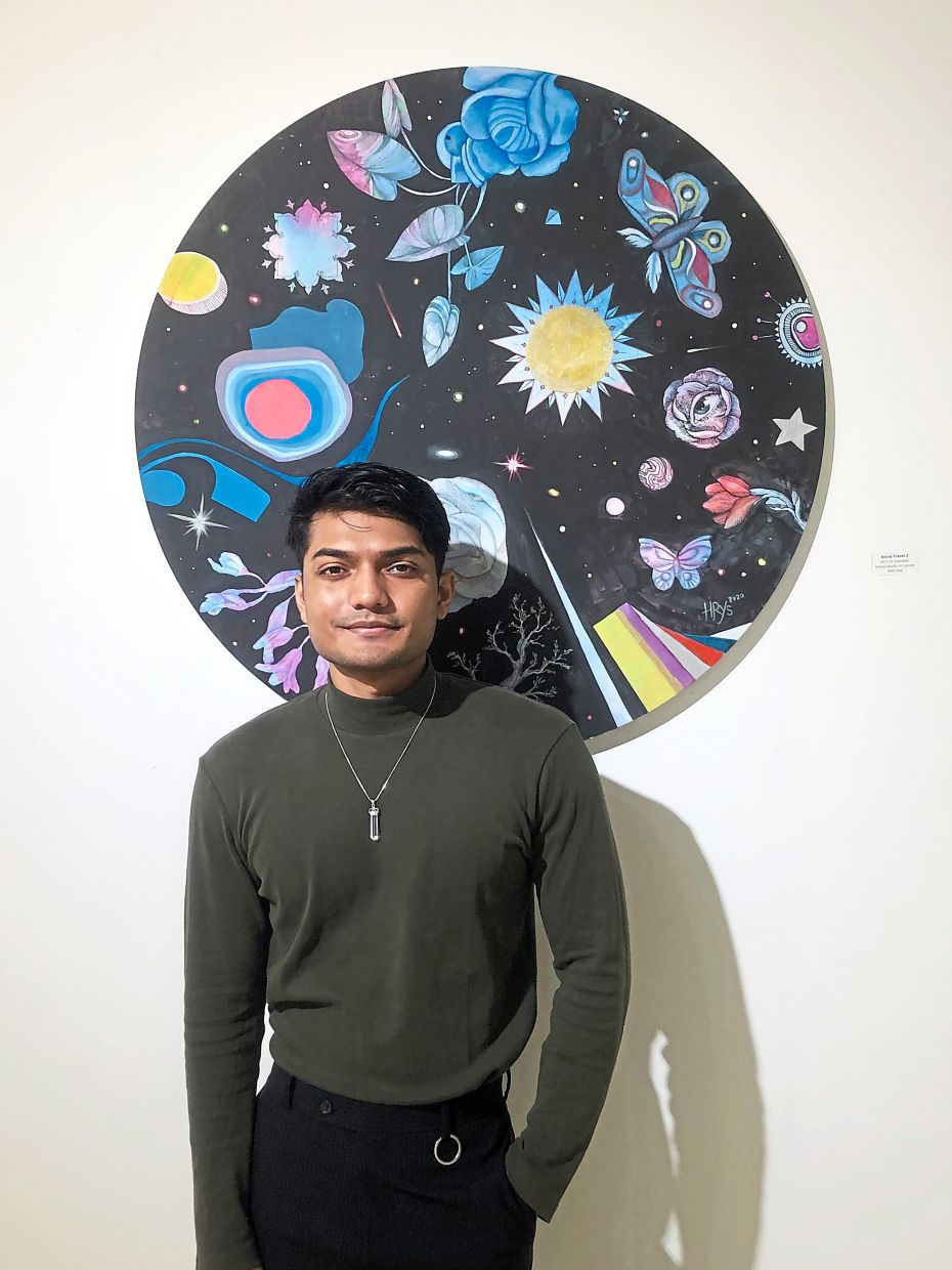 Haris, standing with his artwork titled 'Astral Travel 2' (mixed media on canvas, 2020), says he hopes to reopen this new exhibition once the MCO is lifted. Photo: Zhan Art Space