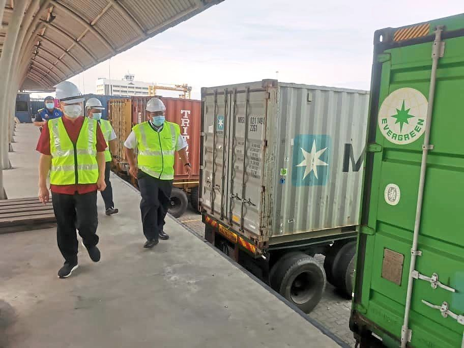 Tan (in red shirt) visiting NBCT to  ensure that cargo clearance runs smoothly. —Filepic