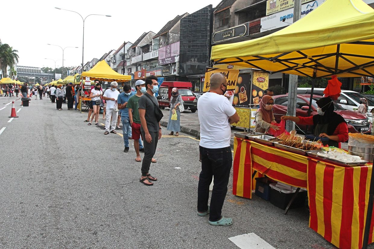 Visitors wearing face masks and practising physical distancing while shopping at the Taman Tun Dr Ismail night market in Kuala Lumpur.