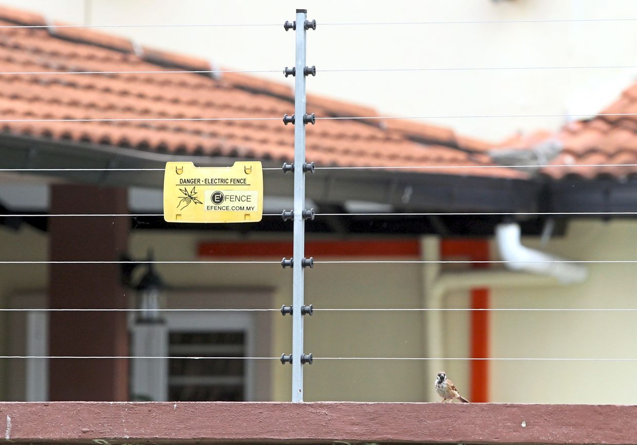 A corner lot in Kelana Jaya spotted with electric fencing and a sign warning of the danger.