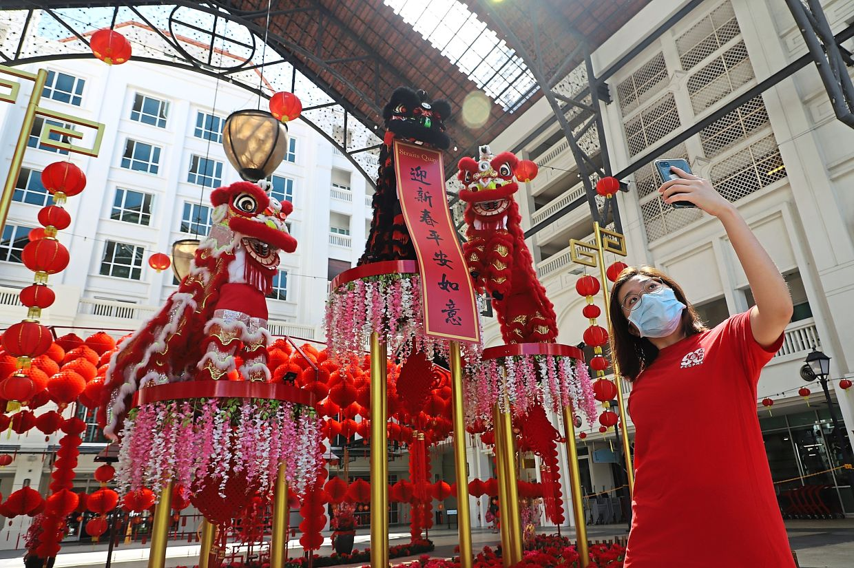 A visitor at Straits Quay taking photos with the display of three lions perched atop platforms surrounded by peonies, weeping willows and lanterns.