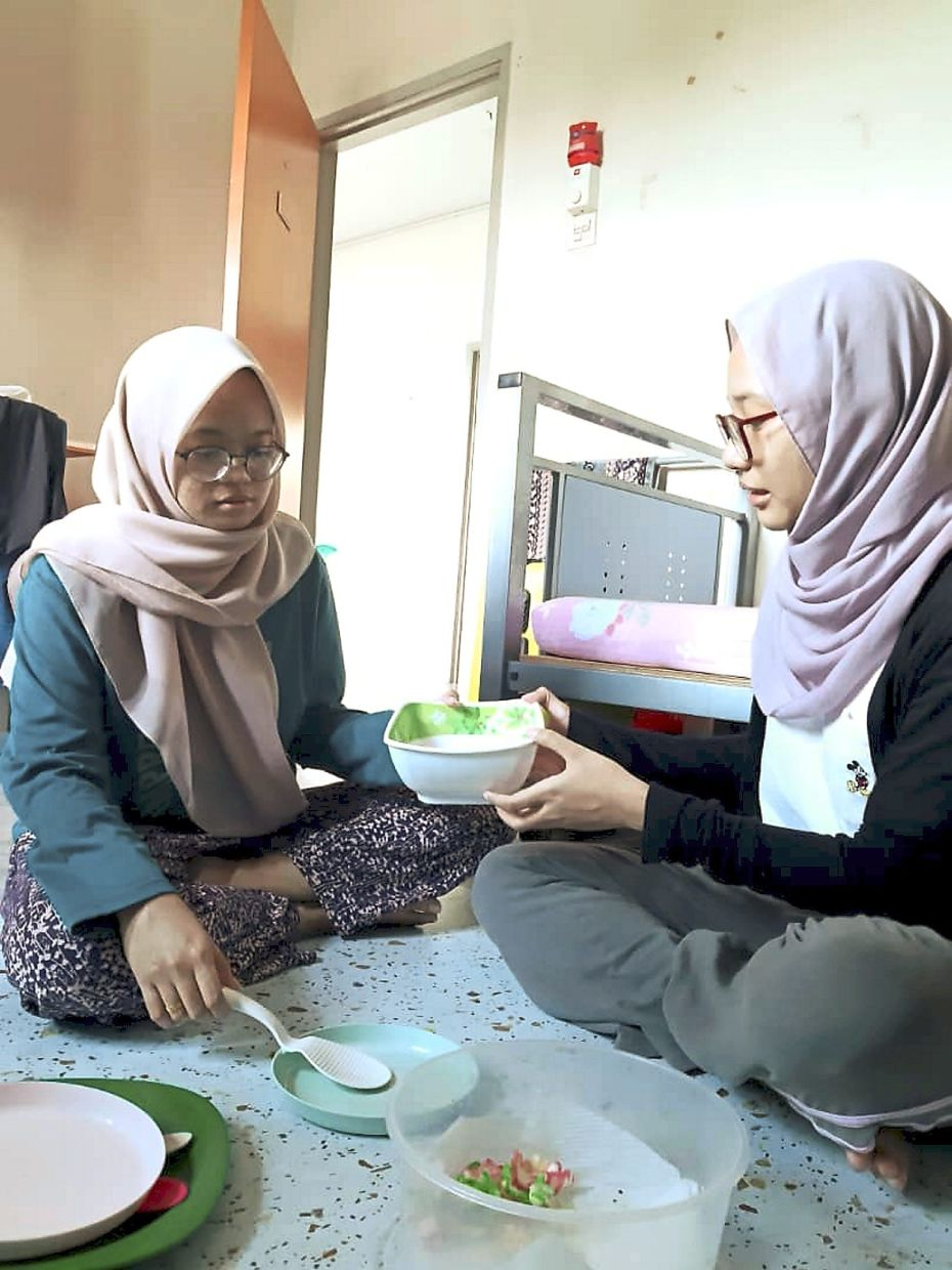Grateful for the food: Aimi Zafirah Husna Hashim (left) and Fatin Humaira' enjoying the food sent over by Shyam Priah.
