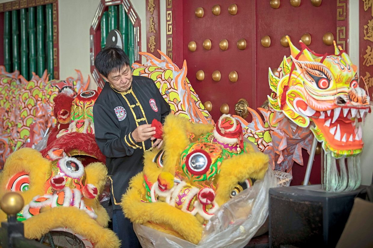 Till next year: Song cleaning a lion's head at the wushu training centre  in Kuching. — ZULAZHAR SHEBLEE/The Star