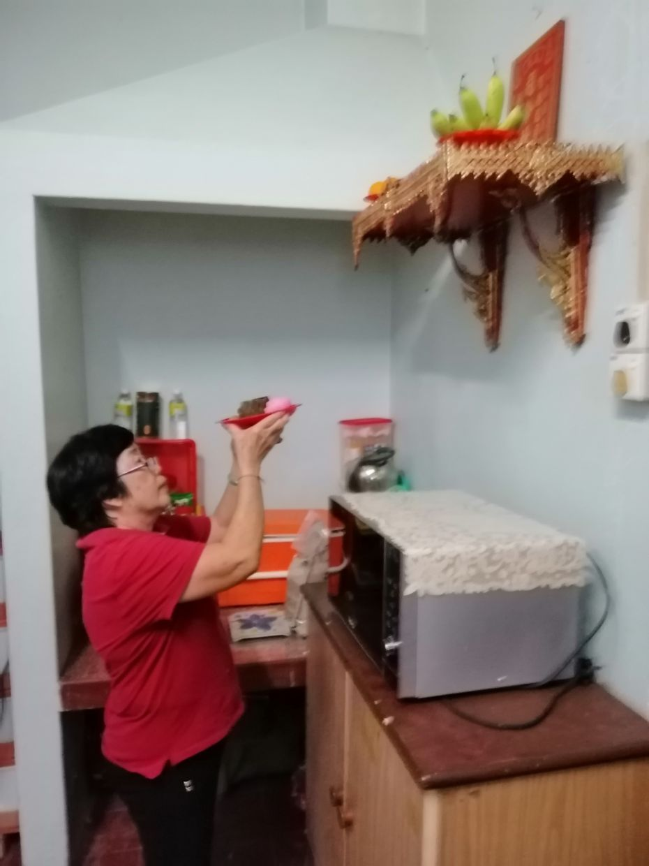 The writer's aunt Chiah Lan Yook offering prayers to the Kitchen God at the family home in Penang. — ANG SENG HIN