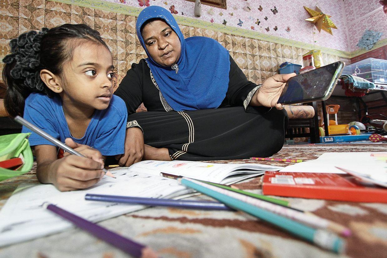 Mazurah guiding her daughter Nur Mashitah with her homework at their home in Taman Manggis.